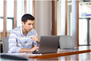 A man using his laptop to research about loan refinancing